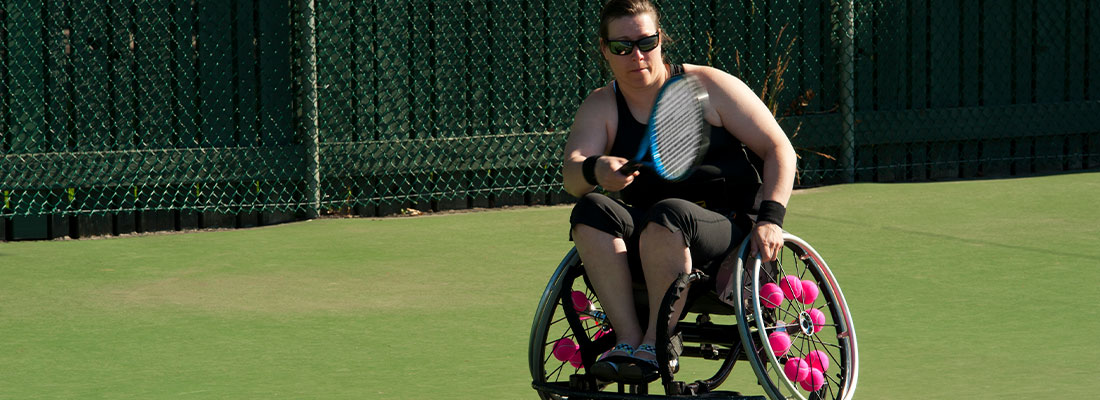 a woman playing wheelchair tennis